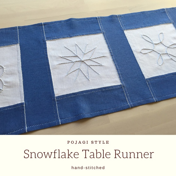 blue and white hand-stitched linen table runner with snowflake designs.