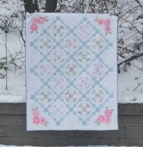 white, blue and pink quilt