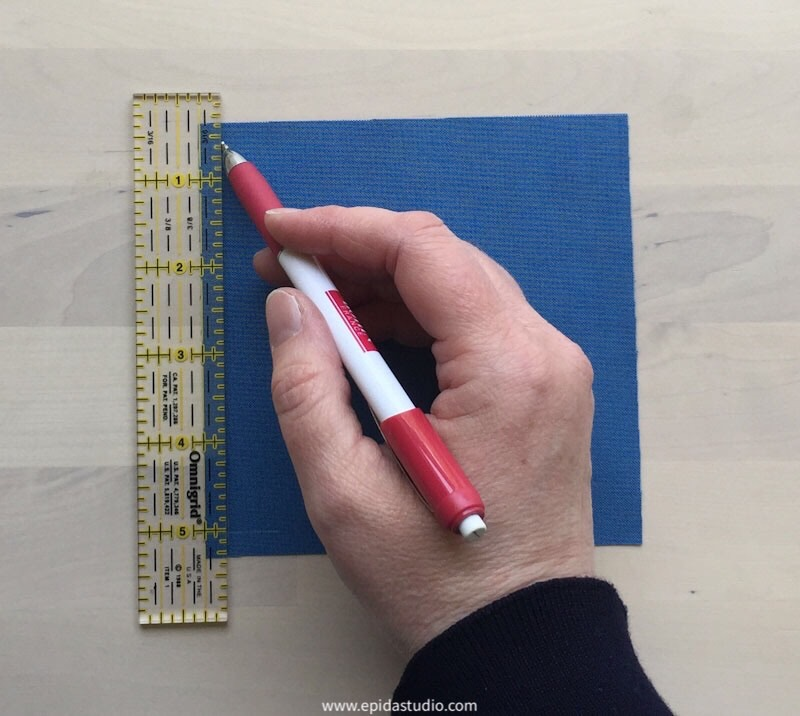 "hand marking a 1/4"" seam allowance on a square of blue fabric."