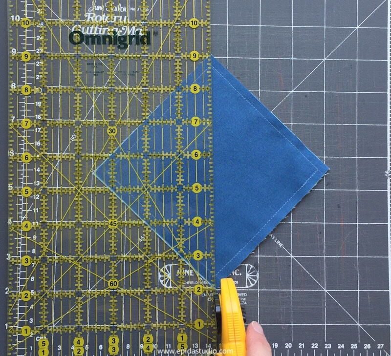 fabric square being cut on the diagonal with a rotary cutter and quilting ruler.