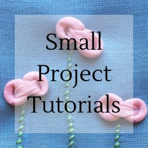 "pink fabric flowers on a blue background with text ""small project tutorials""."