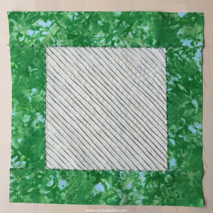 square of pin tucks with green border.