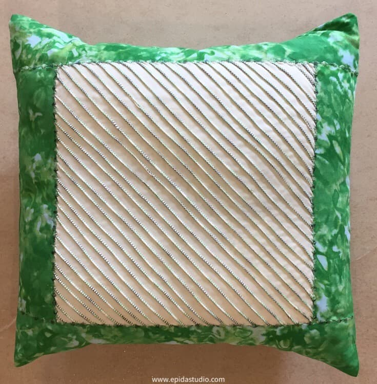 embellished pin tuck pillow in green and white.