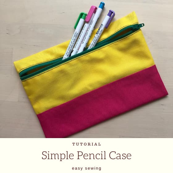 pink and yellow pencil case with pens and title.